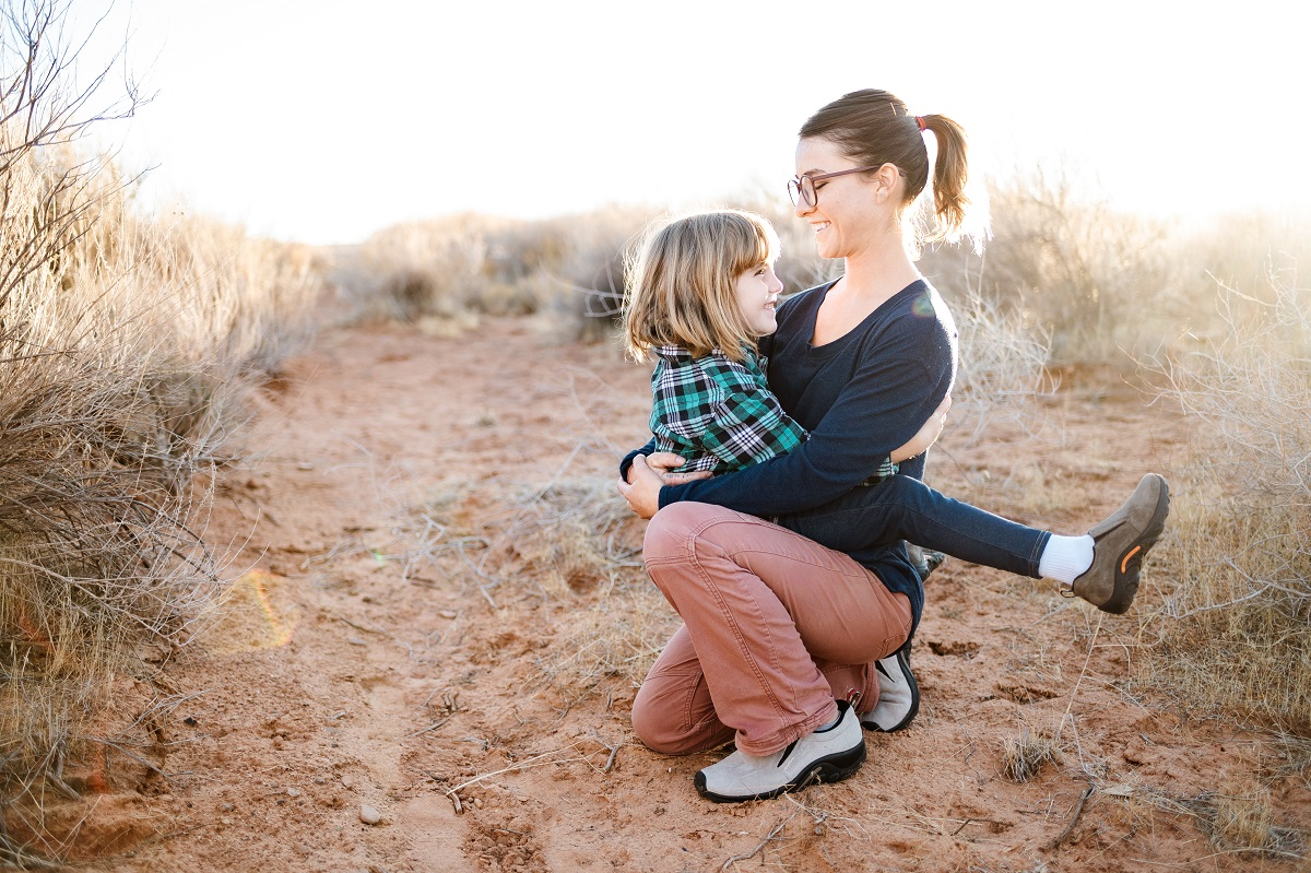 mom and daughter hugging on a hiking trail