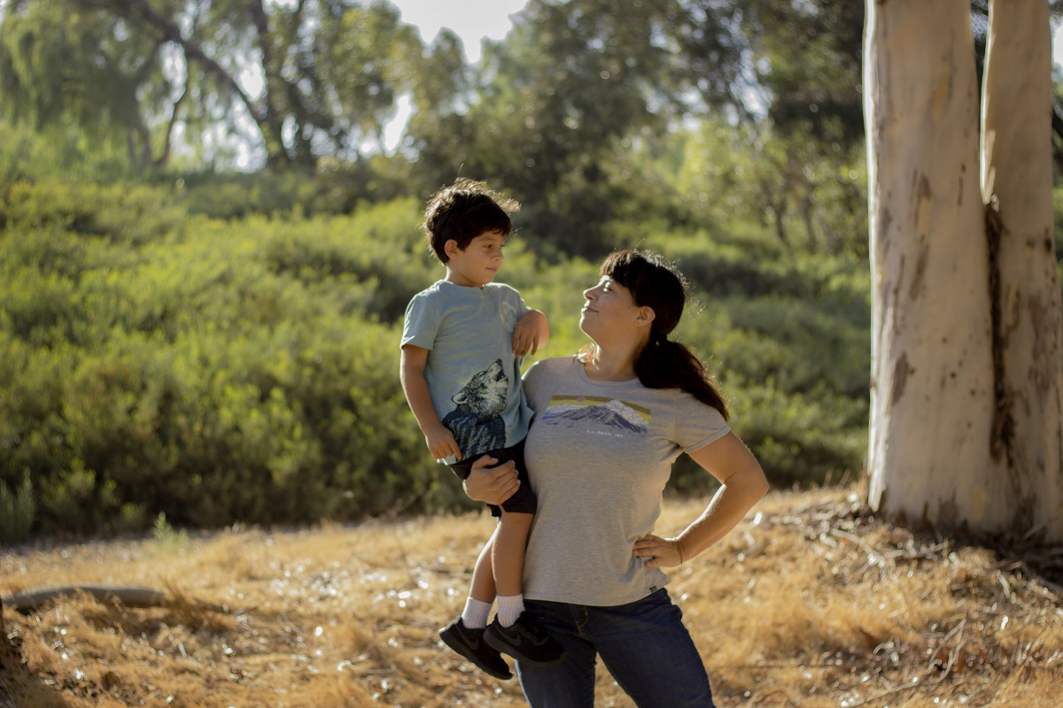 Mom holding young boy outdoors