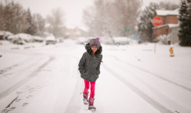 girl walking down a snowy neighborhood street